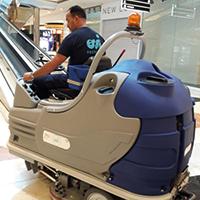 Agent d'entretien Qualifié en train de faire fonctionner une autolaveuse dans un centre commercial