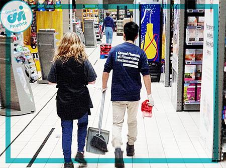 Agent d'entretien en train de nettoyer les allées d'un supermarché