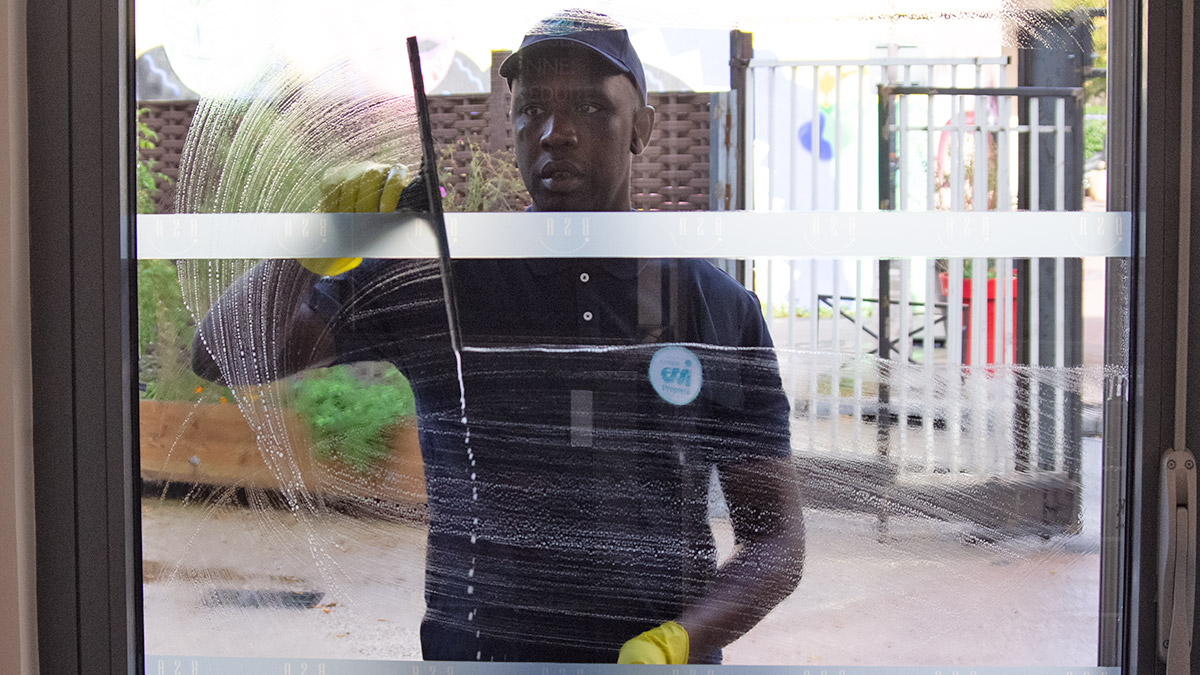 Laveur de vitre en train de nettoyer une porte vitrée