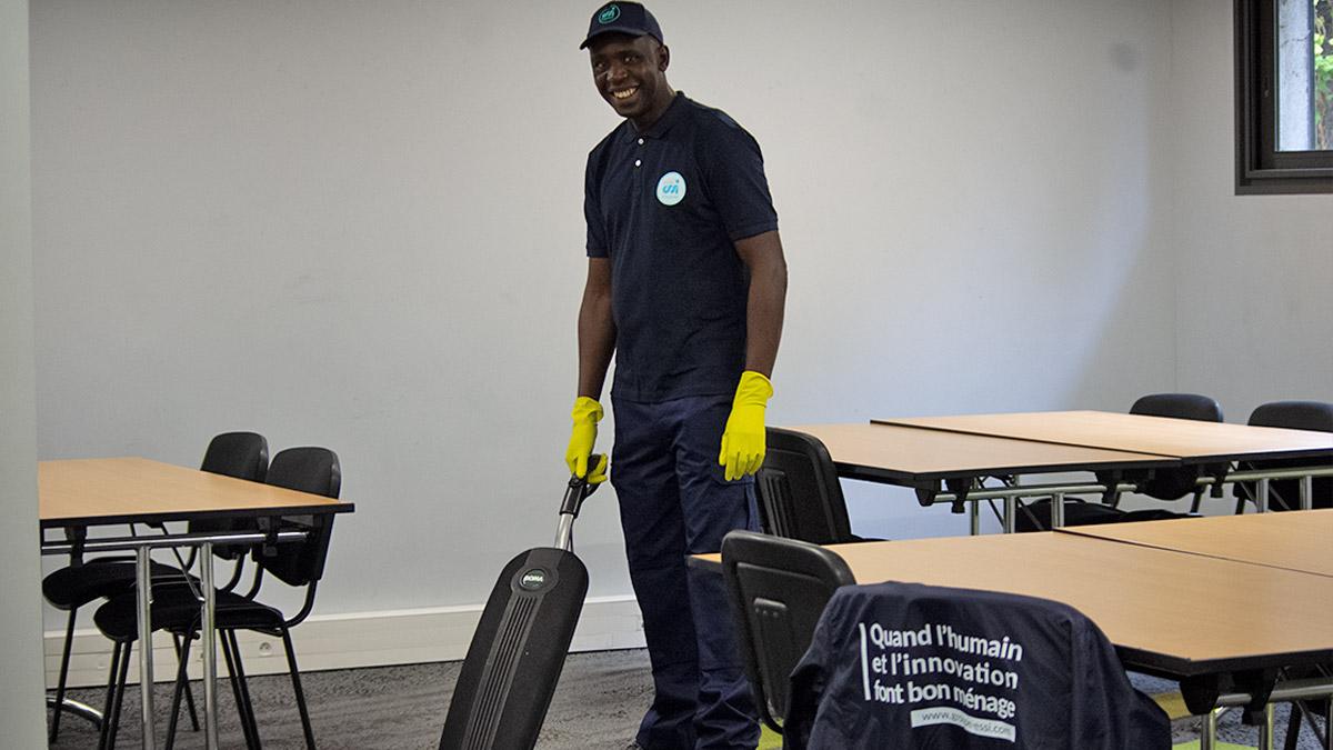 Agent d'entretien en train de passer l'aspirateur dans une salle de classe