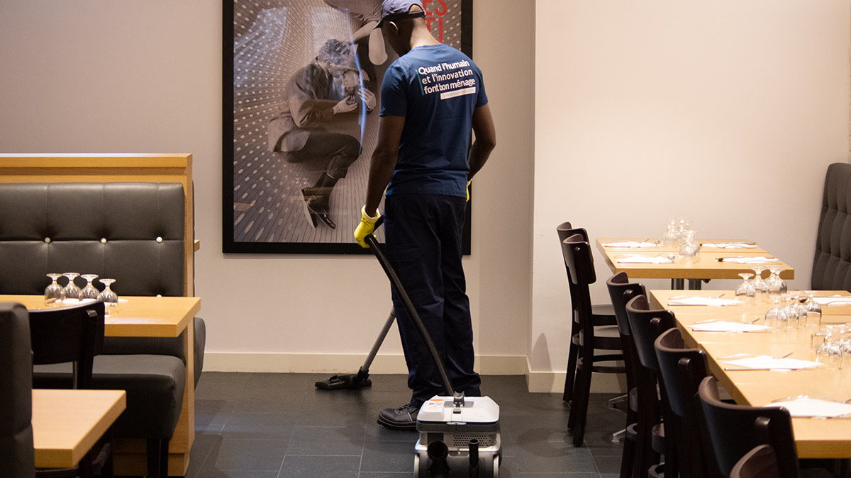 Agent d'entretien qui passe l'aspirateur dans un couloir