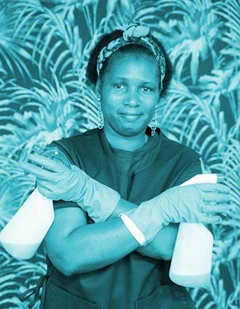 Photo d'illustration - Femme de ménage les bras croisés tenant un pulvérisateur dans chaque main.