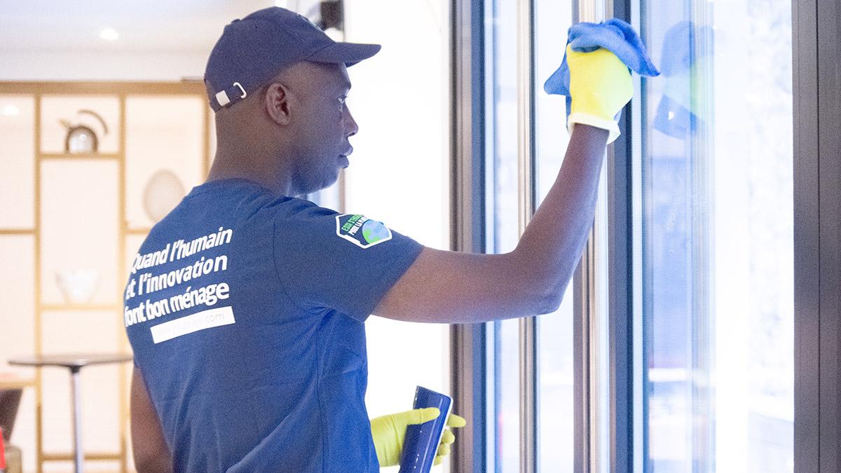 Nettoyage des vitres d'un magasin de luxe par un agent de Propreté