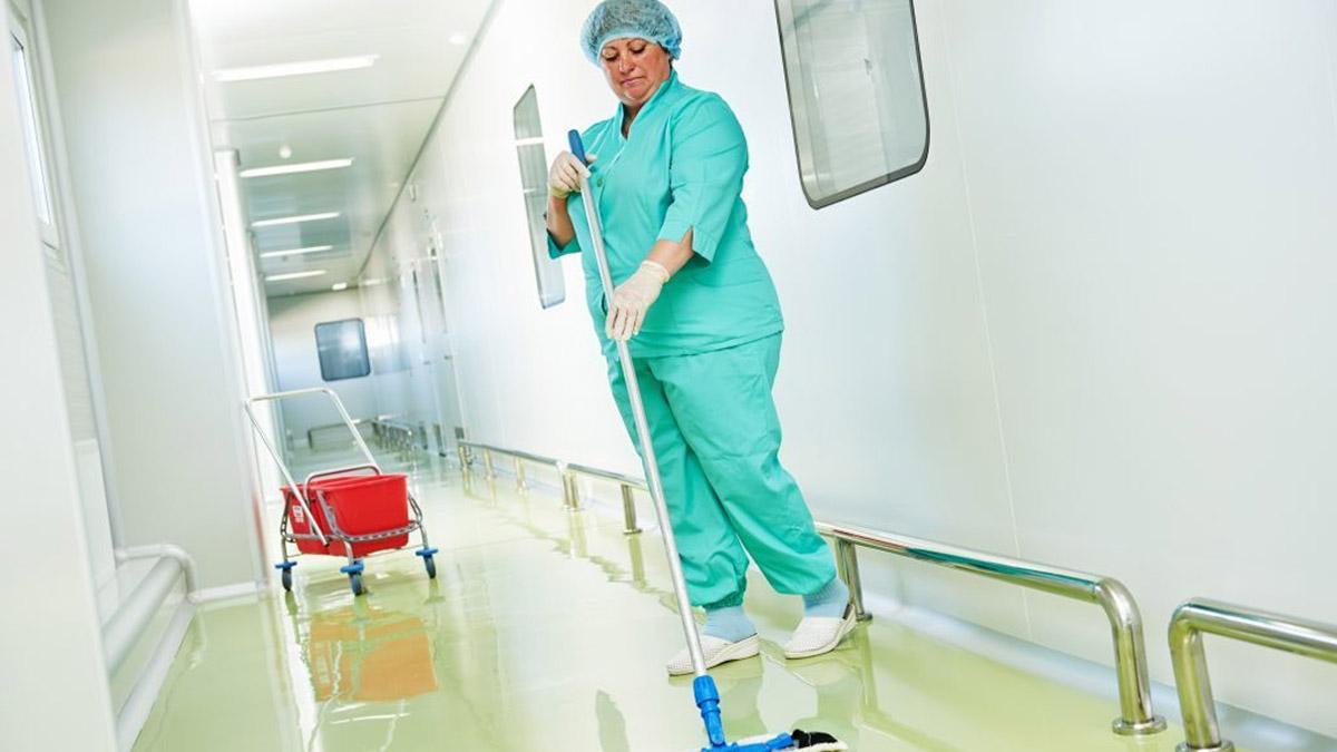 Agent de Propreté dans un couloir en tenue adaptée au secteur de la santé
